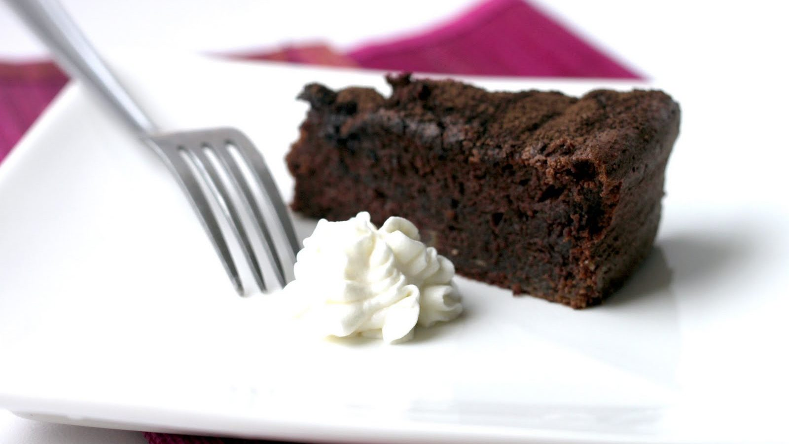 A piece of chocolate cake with cream on white plate with a fork.