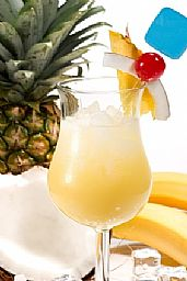 A tall stemmed glass of yellow drink with ice and a pineapple