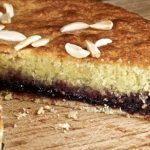 A whole Bakewell Tart , one slice taken out showing the layered inside.