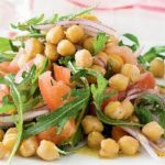 chickpeas, tomatoes, rockets and onion salad heap on white plate