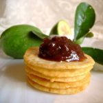 brown feijoa chutney heaped on a stack of crackers with whole feijoas in the back