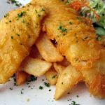 Fish and chips on white plate.