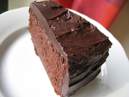 A slice of chocolate frosted chocolate cake on white plate.