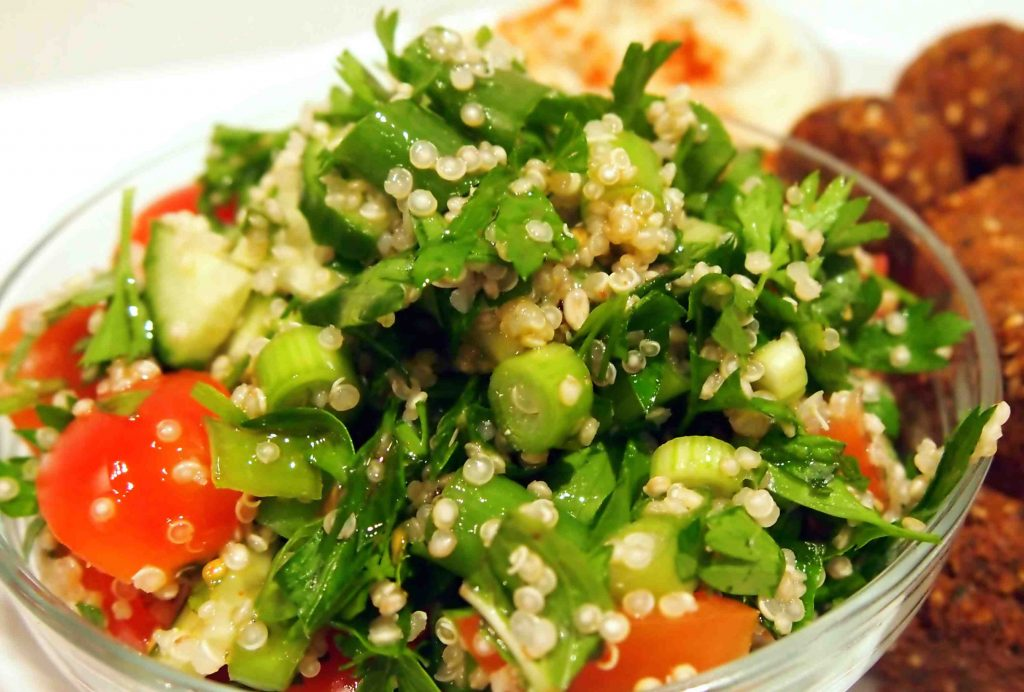 A glass bowl of green leaves, tomatoes and wheat pearls, some cooked balls of food in the back.