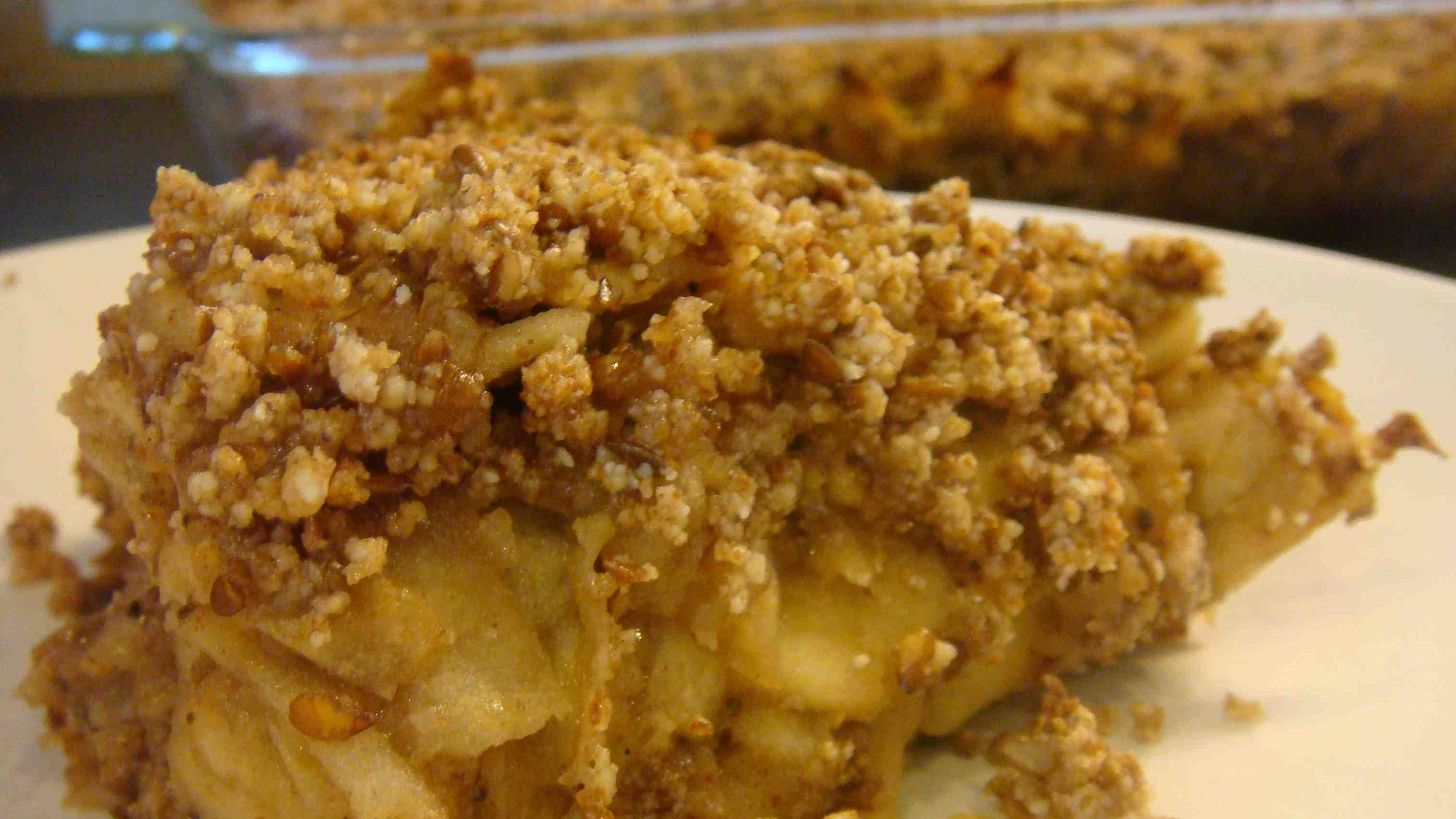 A portion of crumble on a plate in front and the glass baking dish full at rear.