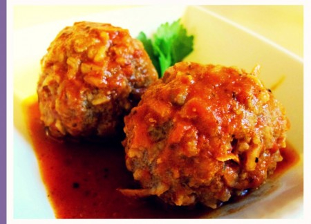 Two tomato sauce covered meat balls with some sauce and herb.
