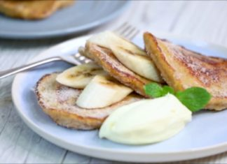 3 round pancakes with banana slices inserted in between and a blob of white cream on blue plate with a fork.