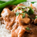 Cooked meat and mushroom with sauce over white rice with green beams.