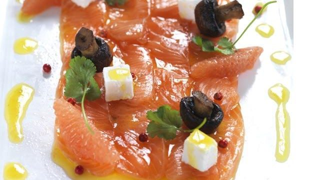 Cured salmon topped with cubes of white food and black olives , drizzle of oil.