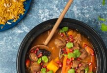 Black pot full of red stew with meat and potato topped with red berries and herbs and a plate of yellow couscous on blue top