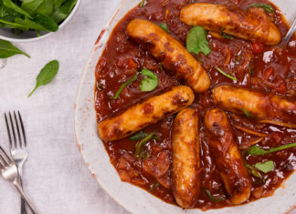 6 sausages in red sauce in a large round bowl.