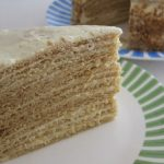 Layered cake cut in wedge on green rimmed plate