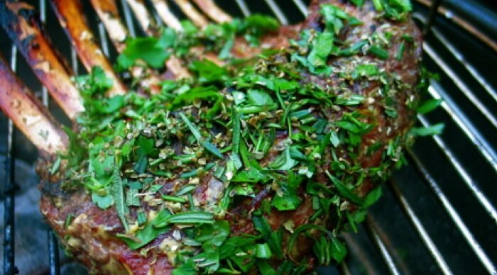 Lamb rack topped with chopped fresh herb on barbeque grill.