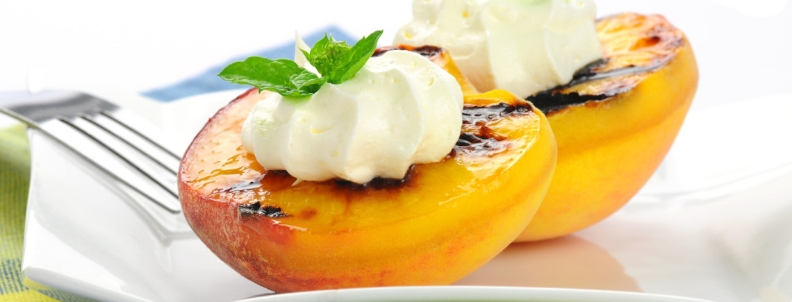 Delicious grilled peaches served with whipped cream.