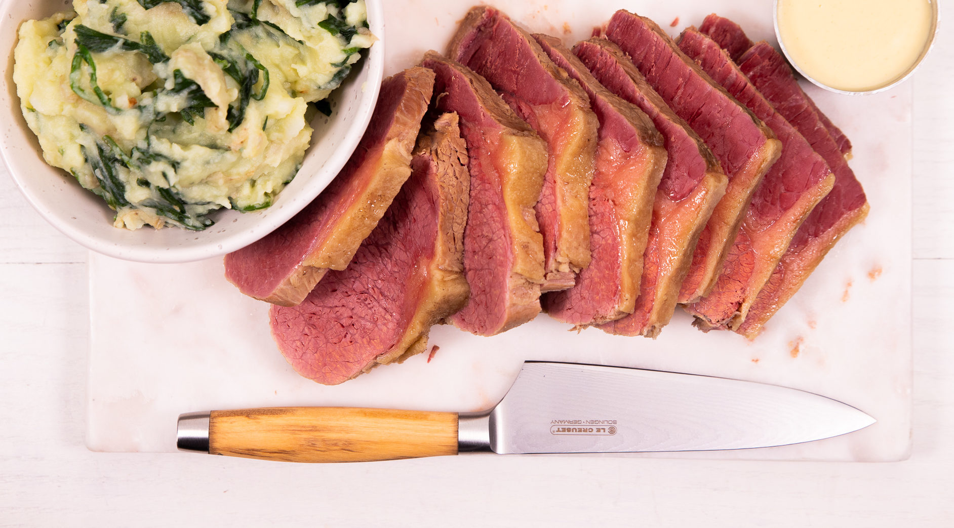 Sliced corned beef on a chopping board with spinach mash