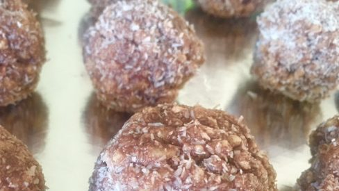Several cocoa balls dusted with white sugar lined up.