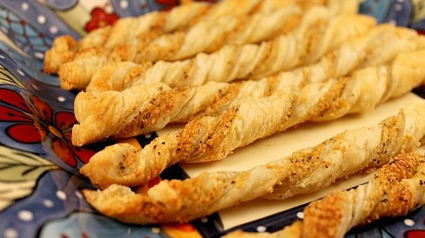 Six baked cheese twist pastries on colourful plate.