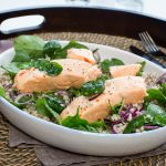Two cooked pieces of salmon on grain and green salad in oval bowl, on a tray with forks.