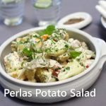A white dish full of potato salad, wine glasses and plates at back.