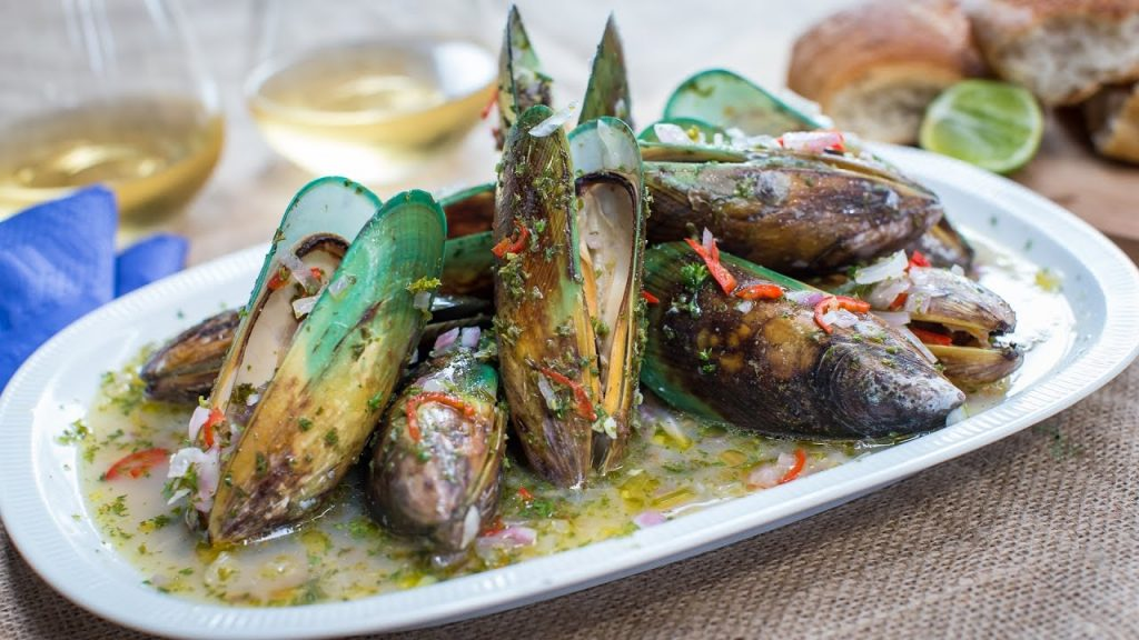 Cooked mussells in shells on platter.