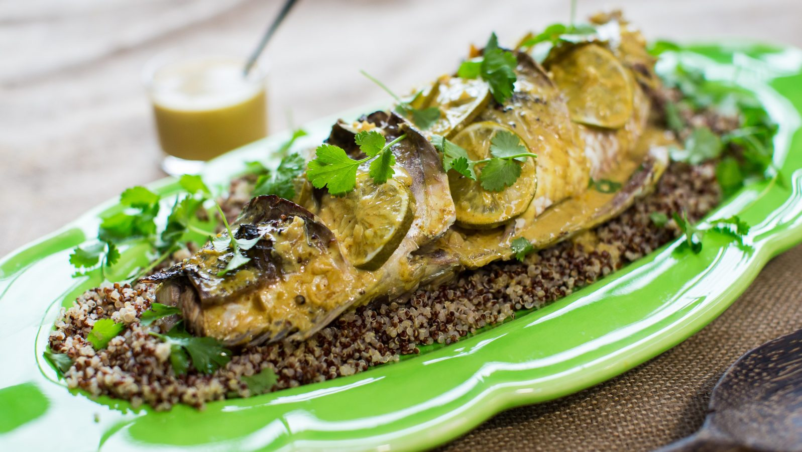 A whole cooked fish topped with yellowish sauce, lemon slices and green herbs on bed of wholegrain mustard on a light green platter, a jar of sauce in the back.