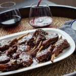 Cooked lamb chops with dark brown sauce on white plate and two glasses of red wine.