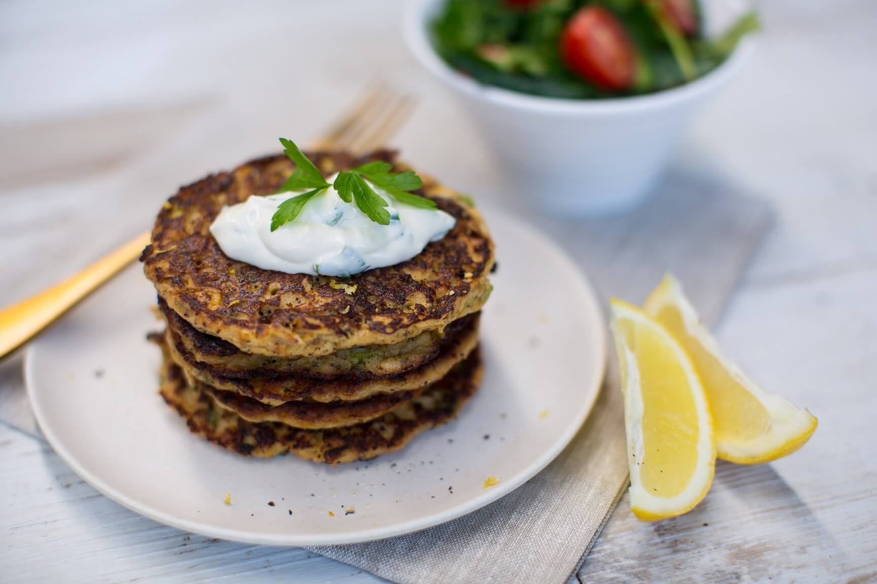 Stack of mussel fritters with a couple of lemon wedges, a fork and a small bowl of salad behind