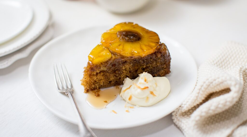 A piece of brown cake with a pineapple ring on top on a white plate with a blob of cream and fork.