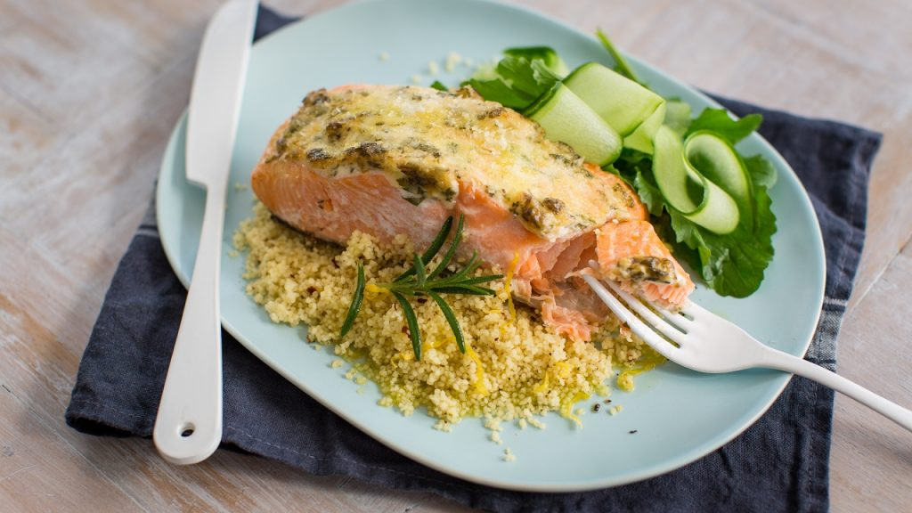 A piece of cooked salmon on yellow couscous and greens on a blue plate.