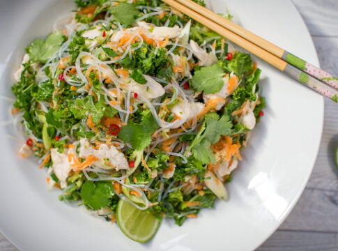 Rice noodle and green salad with red chilli bits and lime halves and chopsticks on white round plate