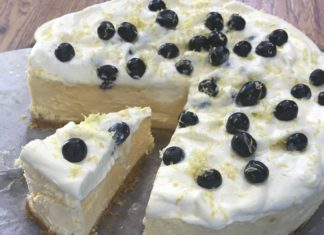A three quarters of white round cake and a wedge slice of it with dark blue fruits on top on wooden board