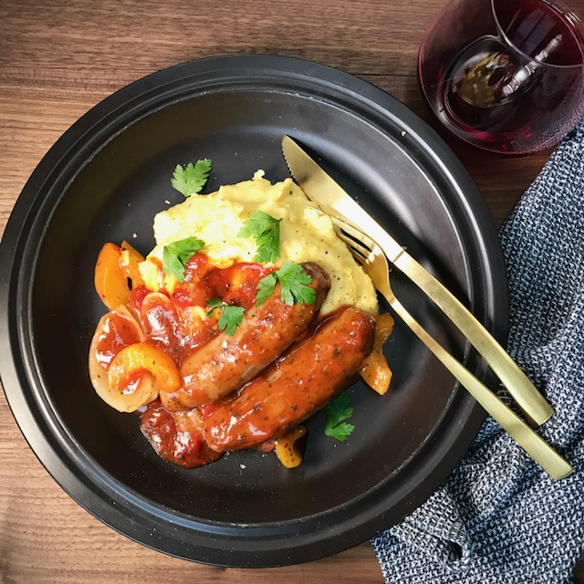 Two sausages in red tomato sauce on mashed potato and peas on a black plate with a knife and fork.
