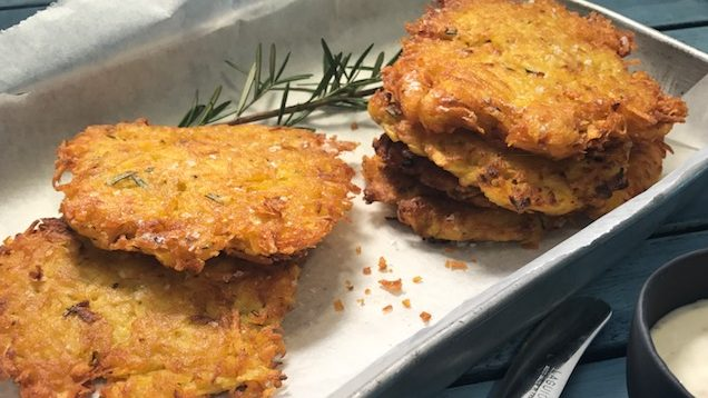 Five round hash browns on paper in a metal tray with sprig of rosemary, and a knife.