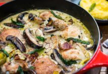 Chicken, mushroom, green beans in creamy coloured sauce in a red handled casserole dish, with a small bowl of soft mashed potato.