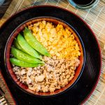 A black round tray with a bowl of eggs, mince and green beans on bamboo mat. chopsticks, small bowl of sauce.