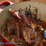 Slow roast lamb in a casserole dish with rosemary and sweet chili sauce