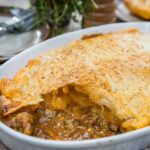 Large oval beef pie and serving plates, forks