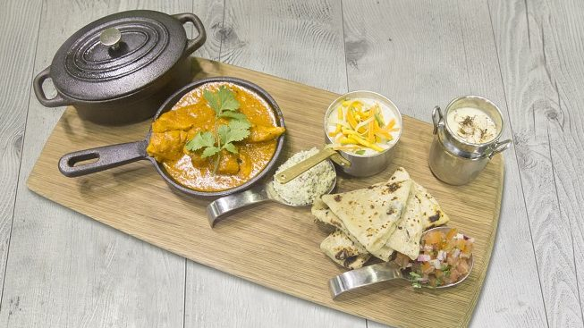 A black pot with a lid on, a dish filled with curry sauce, roti breads and two small dish of food on a mat.