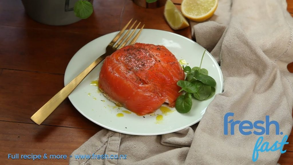 A smoked salmon dome shaped food on a plate with fork and herb.