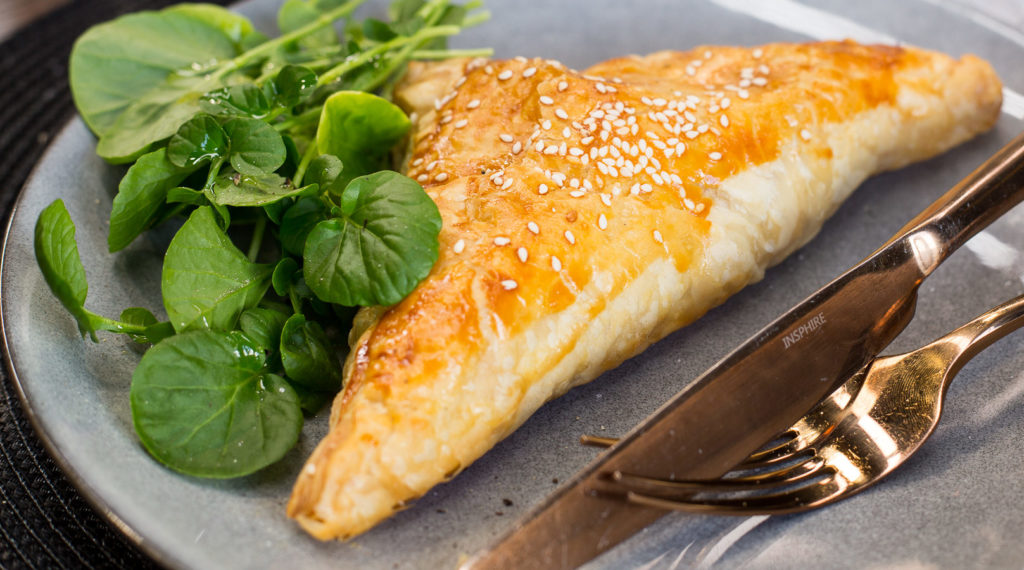 A triangle shaped baked pie on a plate with greens.