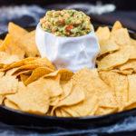 Guacamole in a skull like ramekin surrounded by corn chips