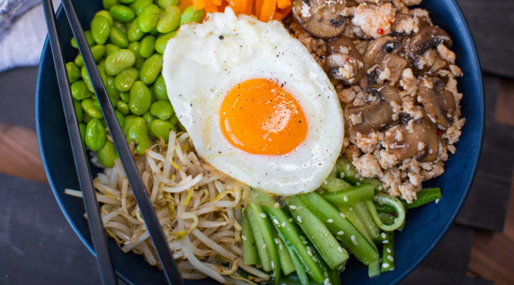 Bowl of chicken, vegetables and a fried egg topped food with chopsticks