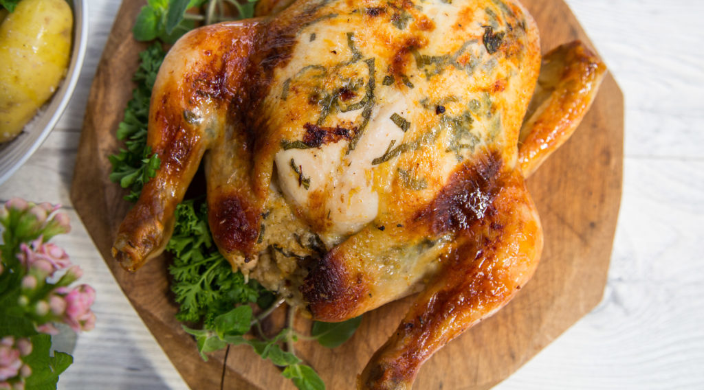 A whole roast chicken with herbs on wooden board.