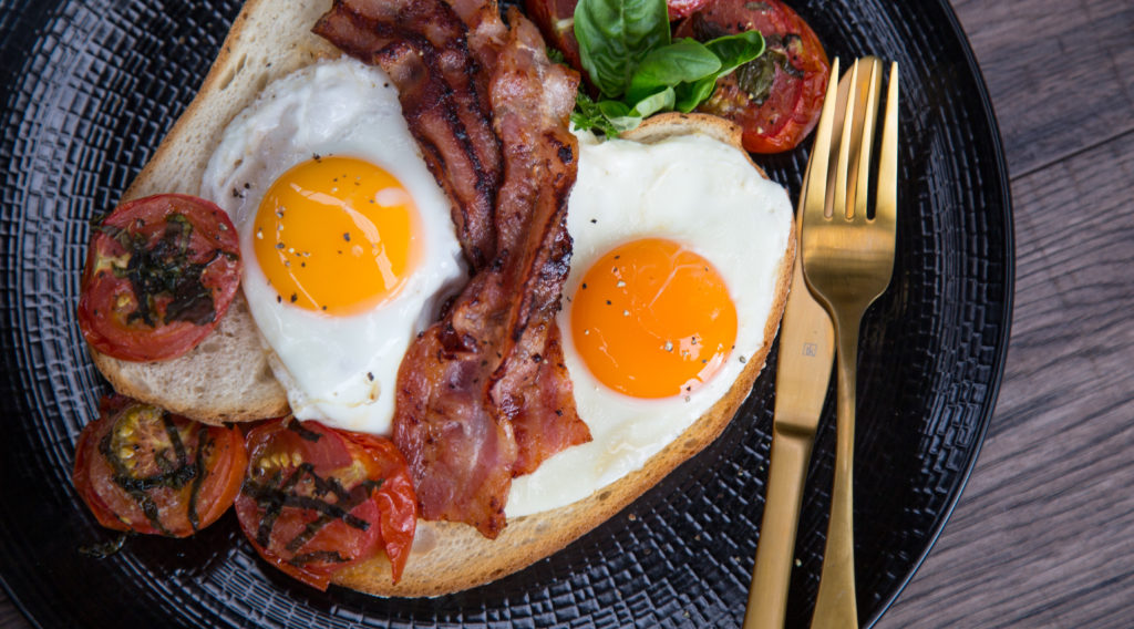Two fried eggs, bacon and cooked tomatoes with herb on a plate with knife and fork.