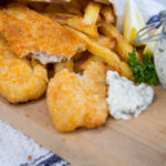 Crumbed fish pieces and chips and jar of tarter sauce on wooden board