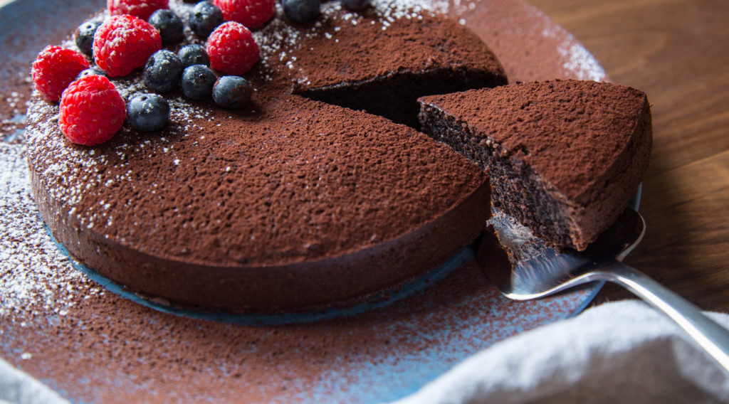 Whole chocolate cake topped with berries, a slice being served out.