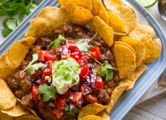 Round corn chips on a platter topped with beef, sauce, red cupsicum pieces, green herb and green mash.fork and spoon on side