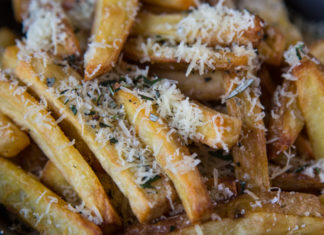 Close up of potato fries covered with grated Parmesan cheese