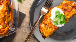 A chicken enchilada with sour cream and coriander on top sitting on a grey plate with a gold fork.