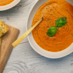 Two bowls of tomato soup topped with herb, and slices of flat bread.